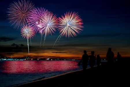 Amazing beautiful colorful fireworks display on celebration night, showing on the sea beach with multi color of reflection on water Stockfoto - 132149326