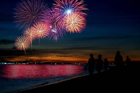Amazing beautiful colorful fireworks display on celebration night, showing on the sea beach with multi color of reflection on water Stockfoto - 132148136