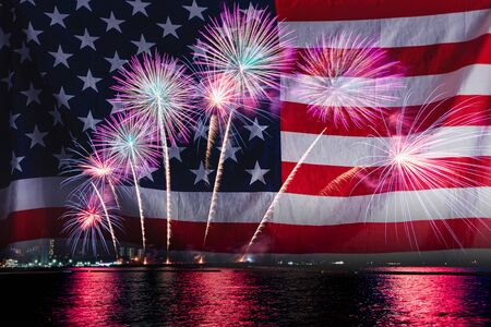 Double exposure of Amazing beautiful colorful fireworks display on celebration night with USA flag, showing on the sea beach with multi color of reflection on water. 4th July Independence day concept