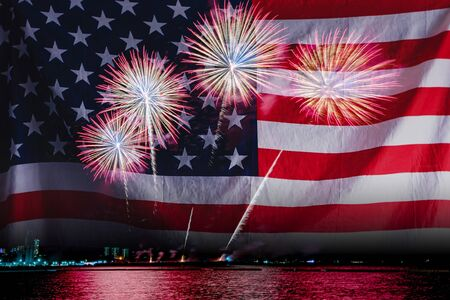 Double exposure of Amazing beautiful colorful fireworks display on celebration night with USA flag, showing on the sea beach with multi color of reflection on water. 4th July Independence day concept Stockfoto - 132149114
