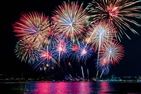 Incroyable beau feu d'artifice coloré le soir de la célébration, montrant sur la plage de la mer avec plusieurs couleurs de réflexion sur l'eau