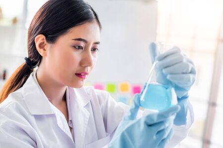 Attraktiver junger asiatischer Wissenschaftlerfrauenlabortechnikerassistent, der Probe im Reagenzglas im Labor analysiert. Medizinisches, pharmazeutisches und wissenschaftliches Forschungs- und Entwicklungskonzept.