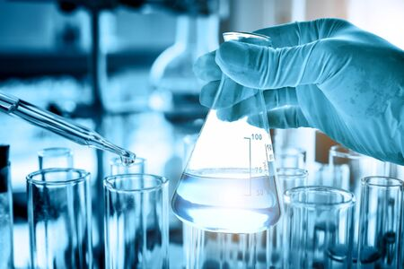 hand of scientist holding flask with lab glassware and test tubes in chemical laboratory background, science laboratory research and development concept Banco de Imagens