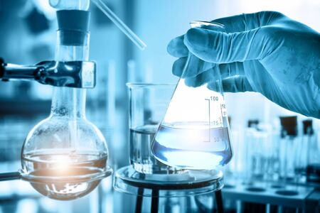 hand of scientist holding flask with lab glassware and test tubes in chemical laboratory background, science laboratory research and development concept Foto de archivo