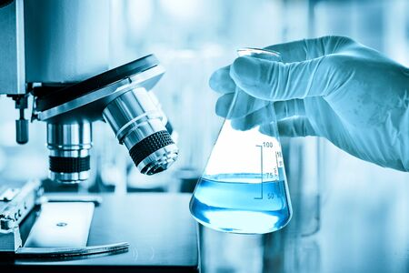 hand of scientist holding flask with lab glassware and test tubes in chemical laboratory background, science laboratory research and development concept