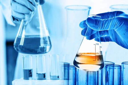 hand of scientist holding flask with lab glassware and test tubes in chemical laboratory background, science laboratory research and development concept Stock fotó