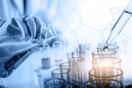 hand of scientist holding flask with lab glassware in chemical laboratory background, science laboratory research and development concept Banco de Imagens