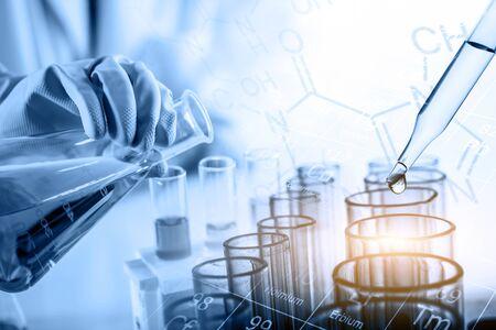 main de scientifique tenant une fiole avec de la verrerie de laboratoire dans un contexte de laboratoire chimique, concept de recherche et développement de laboratoire scientifique Banque d'images