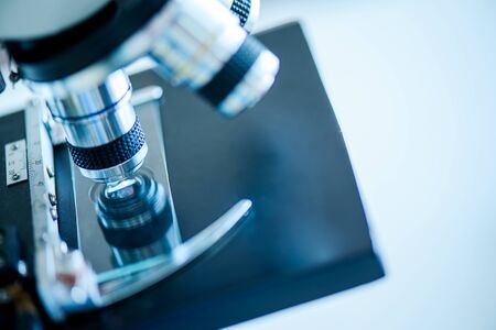 Microscope with lab glassware and dropping chemical liquid to test tube in chemical laboratory background, science laboratory research and development concept Foto de archivo