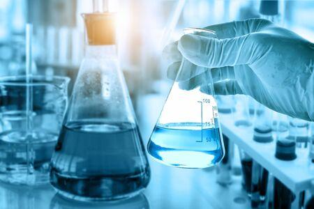 main de scientifique tenant une fiole avec de la verrerie de laboratoire dans un contexte de laboratoire chimique, concept de recherche et développement de laboratoire scientifique