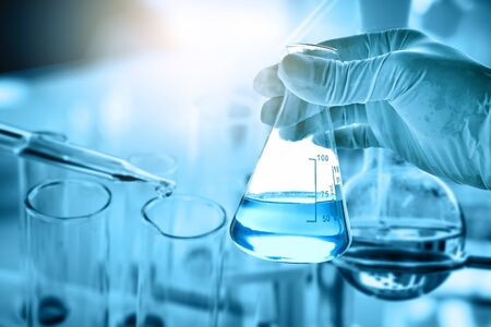 hand of scientist holding flask with lab glassware in chemical laboratory background, science laboratory research and development concept Standard-Bild