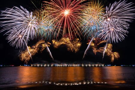 Amazing beautiful colorful fireworks display on celebration night, showing on the sea beach with multi color of reflection on water Фото со стока - 150183930