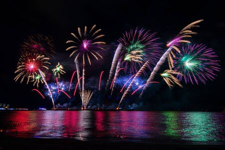 Amazing beautiful colorful fireworks display on celebration night, showing on the sea beach with multi color of reflection on water Фото со стока - 150184008