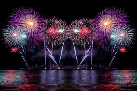 Amazing beautiful colorful fireworks display on celebration night, showing on the sea beach with multi color of reflection on water Фото со стока - 150184206