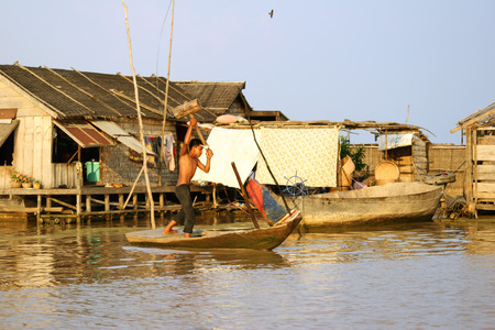 tonle sap: CAMBODIA-APRIL 2005  Cambodian boy repairs his boat with the help of a big mallet near the fishing village of Tonle Sap Lake around April 2005 in Cambodia  Living conditions in the area are difficult