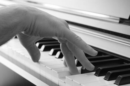 interpretation: Closeup of a hand playing the piano Stock Photo