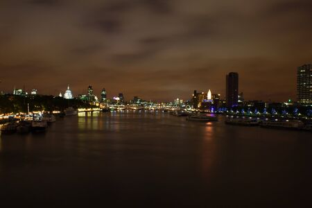 London night view of the thames, with boats and dramatic sky photo