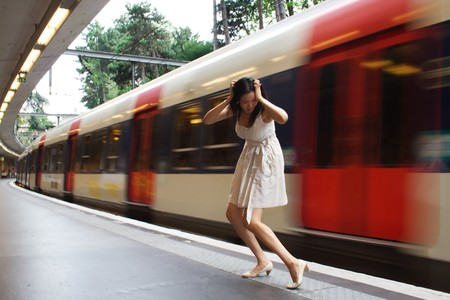 missed: A woman has just missed her train. Shes holding her head as the train departs. Stock Photo