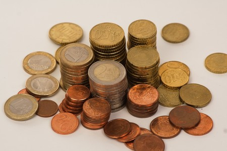 Piles and spread euro coins over white background photo