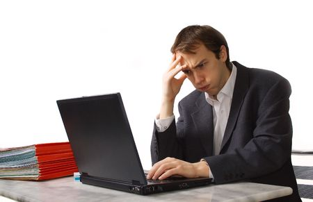 Young man works on laptop, close to breakdown, isolated over white Фото со стока