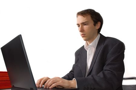 Concentrated young man works on laptop, isolated over white photo