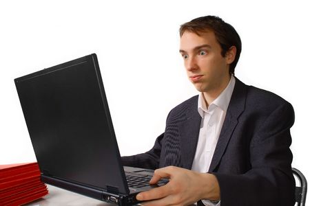 Young man holds laptop and cannot take more, isolated over white
