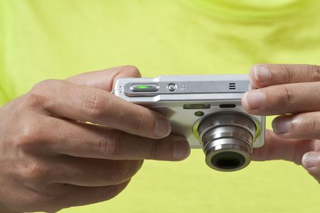 Closeup on hands holding a digital camera while reviewing pictures