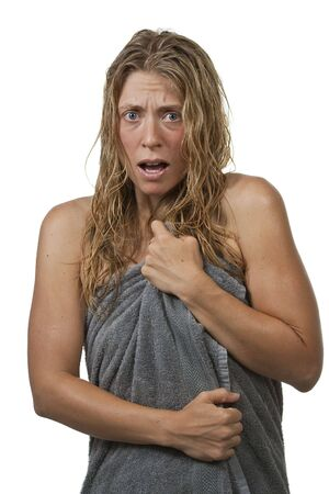 Blond woman with curly hair is surprised and scared while getting out of the shower, grabs her towel. Maybe it's an intruder, or her voyeurist neighbour through the window.