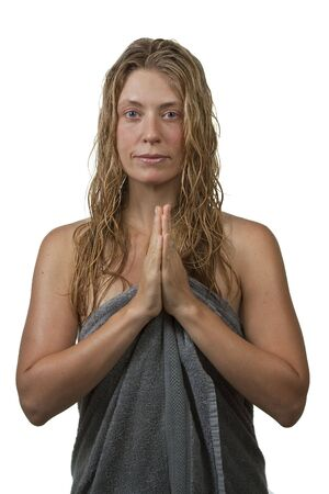 Blond woman out of bath in spa, relaxing, looking at camera with joined hands