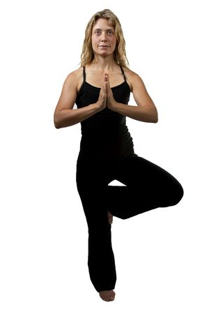Yoga tree pose, called Vrksasana. Blond woman in black outfit standing on one foot hands joined