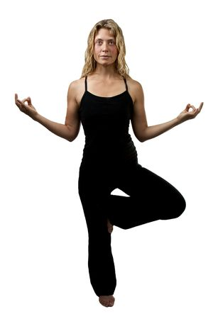 Yoga pose, blond woman in black outfit standing one foot, hands appart Zdjęcie Seryjne