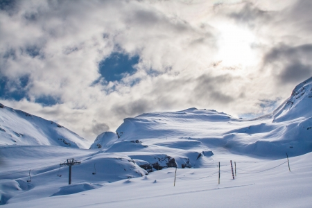 Snowy mountain with huge white cloud above and a ski lift in the foreground Stock Photo - 15978106