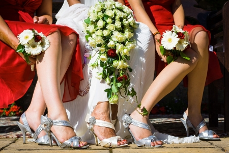 Feet of the bride among two bridesmaids sitting on chairs holding white flower bouquet in their lap and wearing beautiful shoes