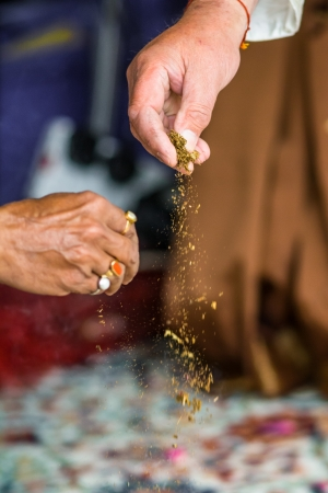 In Haldi ceremony, which is celebrated the day before the indian wedding ceremony, two hands is sprinlking turmeric powder Stock Photo - 15978107