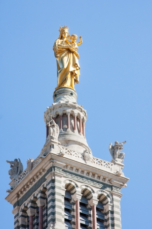 A golden statue of the Madonna holding the little Jesus on the top of a tower of the basilica, Notre-Dame de la Garde in Marseilles, in a sunny day with clear blue sky in the background