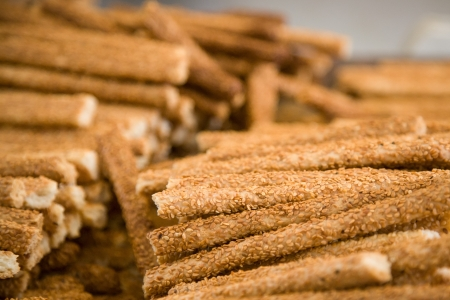 Close up photo of lots of sesame sticks in a pile in a counter of a shop