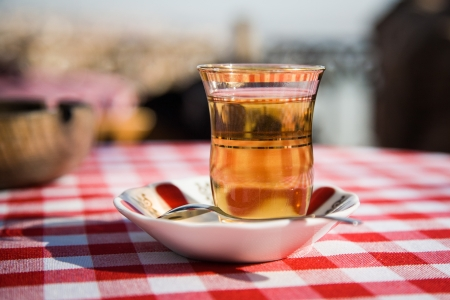 Close up photo of a glass of turkish tea on saucer placed on a table which is covered by a red checked table cloth in a sunny day