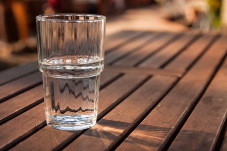 standing water: Close-up picture of a glass of water which is half-full standing on a brown wooden table and as the sun shines through the glass the reflection can be seen on the table