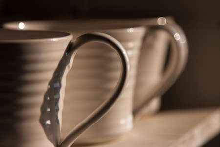 Close-up photo of the handles of white mugs in half-shadow on a shelf
