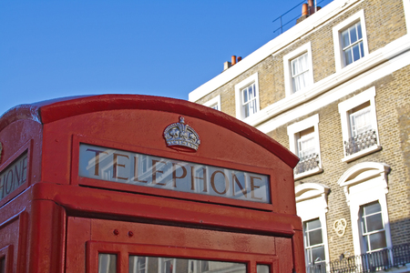 Red telephone booth in London over blue sky and in front of building