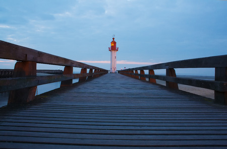 Walkway and lighthouse at sunset in Trouville, Normandy, France Zdjęcie Seryjne