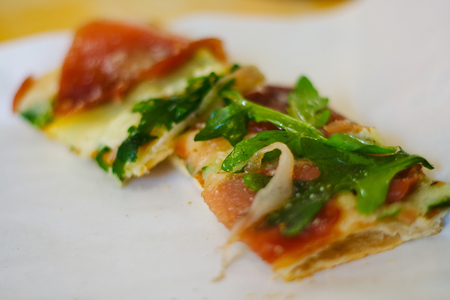Pizza strip on white background, with rocetta salad and ham