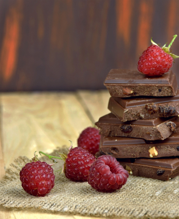 screen savers: Ripe raspberries and chocolate pieces on wooden background. Close-up. Sweet Tooth. Taste of life.Cooking desserts. Holidays for the stomach. Stock Photo