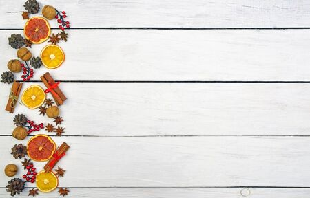 long Christmas ornament made of gingerbread, cones, cinnamon, nuts, anise stars, dried fruits on a wooden background. Christmas background in a rustic style. Top view. Home cosiness. Food background. 写真素材