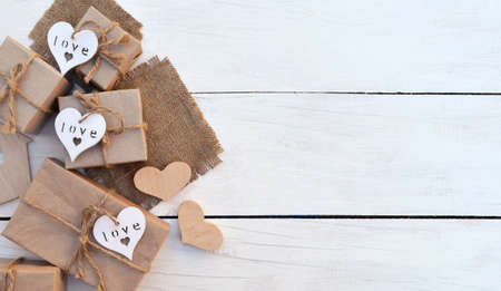 Gift boxes with hearts hand made on a light wooden background. Celebratory background. Christmas New Year. Gifts in a rustic style.