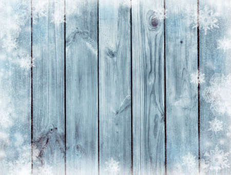 Snow-covered boards and snowflakes. Winter background. Christmas background. New Year wooden background. Top view. Cold season.