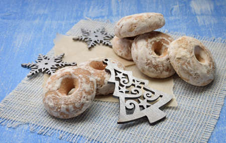 Homemade gingerbread in sugar glaze on a wooden background. Fresh pastries with spices and Christmas tinsel. Made with love. Home cosiness. Celebration atmosphere. Christmas mood. Kitchen background. Food New Year.