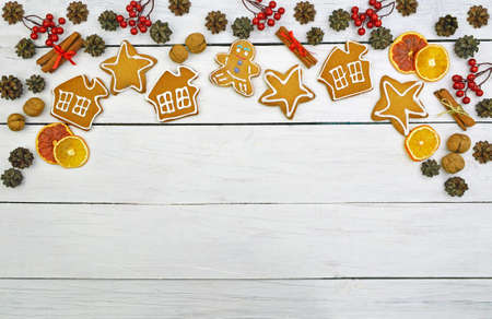 Homemade gingerbread cookies in glaze and festive decor on a light wooden background. top view. Christmas background. Food background.