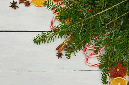Christmas Holiday Background with Gingerbread cookies, Candy Cane and evergreens border over wooden table. Christmas and New year food. Christmas decoration and sweets on light wood background.