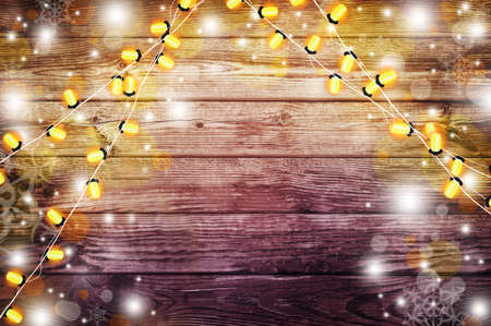 Holiday Lights on the old wooden background. The atmosphere of the holiday. Christmas party. New Year background.